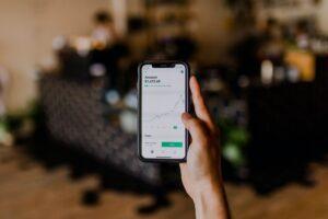 """Investimentos: a imagem mostra uma mão segurando um celular. Na tela, há gráficos e a palavra """"Amazon""""."""
