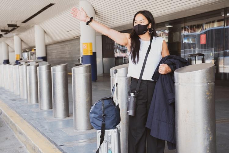 Na imagem, uma mulher com máscara e malas acena, pedindo um táxi, em frente a um aeroporto.